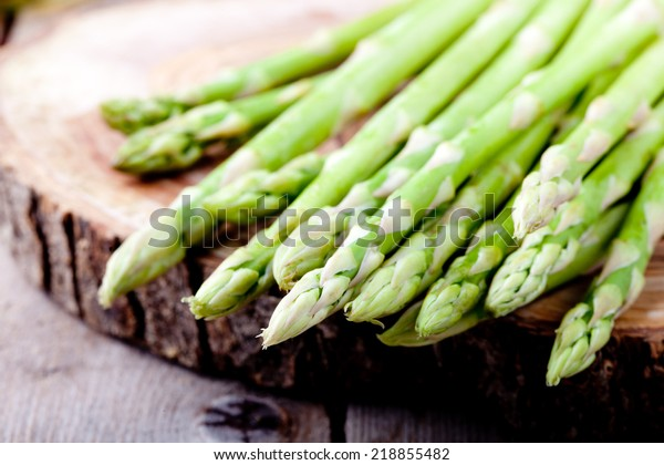 Bunch of fresh asparagus on a wooden background