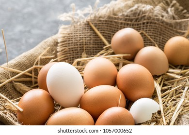 bunch of fresh brown eggs and some straw in a wooden crate