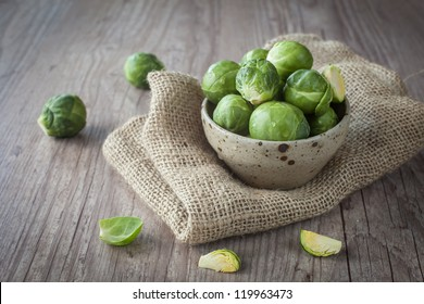 Bunch of fresh Bruxelles sprouts in a cup on wooden background