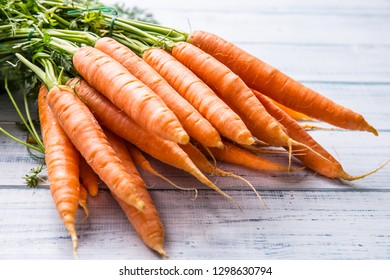 Bunch of fresh carrot on wooden table.