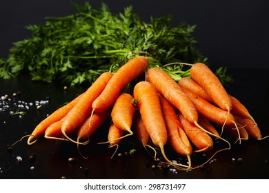 Bunch of fresh carrots with green leaves on wooden table