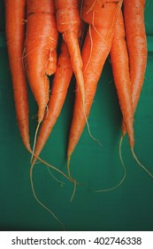 Bunch of fresh carrots without green leaves over green wooden background, top view