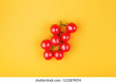 Bunch of fresh cherry romatoes on yellow background. Top view, minimal styled composition.