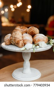 A bunch of fresh croissants covered with sugar powder on a wooden white pedestal in a restaurant with some white flowers as a decoration