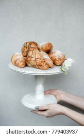 A bunch of fresh croissants covered with sugar powder on a wooden white pedestal held in hands against a grey wall
