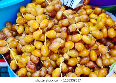 Bunch of fresh Date Palm or Dactylifera (Phoenix) selling in the fruit market for Eid Mubarak festival celebrate day, healthy fruit for fasting and symbolic of celebrate for Muslim people concept