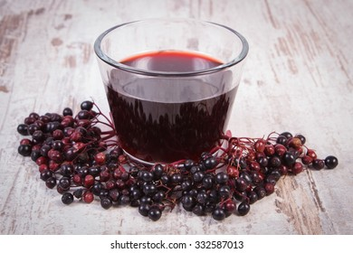Bunch of fresh elderberry and glass of elderberry juice on old rustic wooden background, healthy nutrition, alternative medicine and therapy