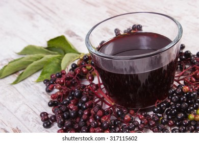 Bunch of fresh elderberry with green leaves and glass of elderberry juice on old rustic wooden background, healthy nutrition, alternative medicine and therapy