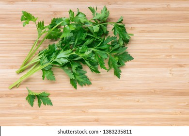 bunch of fresh flat leaf parsley leaves on wooden chopping board with copy space