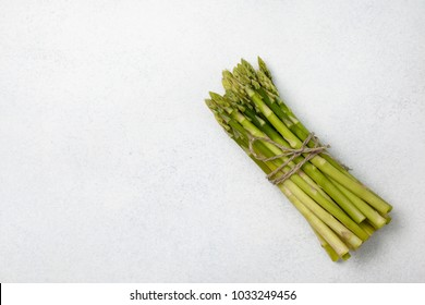 bunch of fresh green asparagus on a light gray background. view from above
