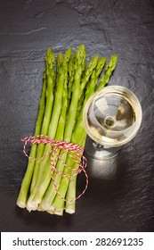 A bunch of fresh green Asparagus on Slate, with a glass of White Wine.