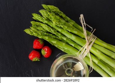 A bunch of fresh green Asparagus on Slate, with a glass of White Wine and Strawberries.