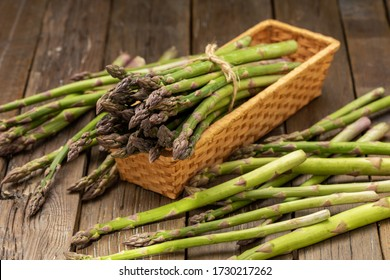 Bunch of fresh green asparagus spears in basket on a rustic wooden table.