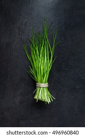 Bunch of fresh green chives on dark gray slate background