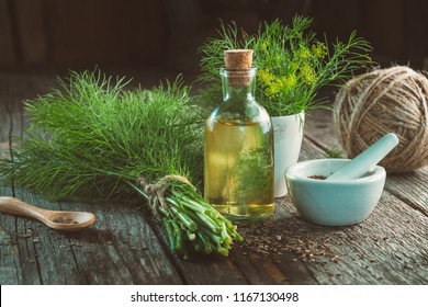 Bunch of fresh green dill, mortar of fennel seeds, bottle of dill oil and jute on wooden board.