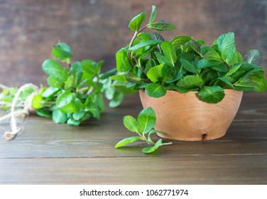 Bunch of Fresh green organic mint leaf on wooden table.