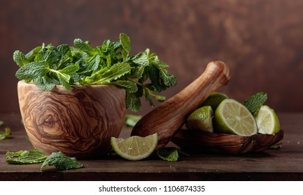 Bunch of fresh green organic mint and lime on old wooden table.Copy space.