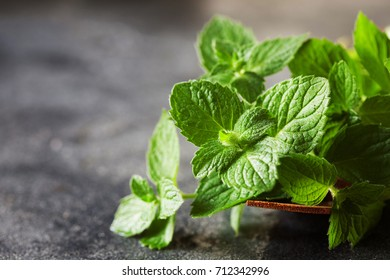 Bunch of fresh green organic mint leaf on black background, selective focus
