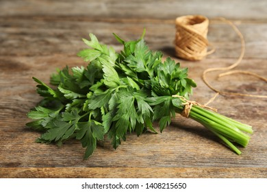 Bunch of fresh green parsley and twine on wooden table