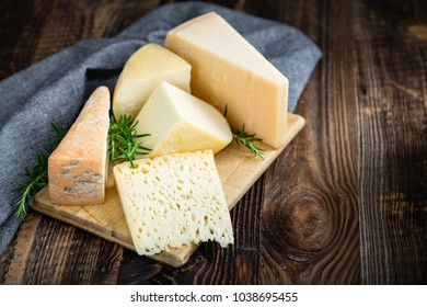 Bunch of fresh  high - quality cheeses from dairy with basil and rosemary.