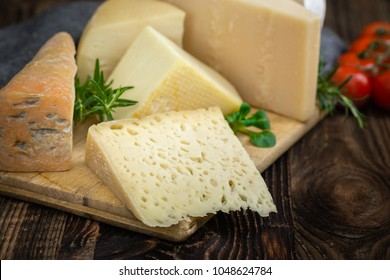 Bunch of fresh  high - quality cheeses from dairy with basil, rosemary and tomatoes.