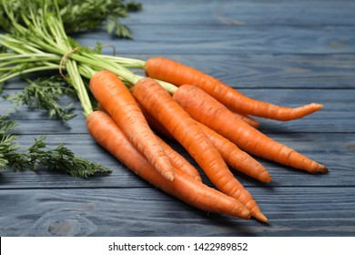Bunch of fresh juicy carrots on wooden background