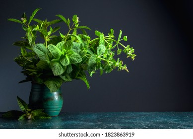 Bunch of fresh mint in an old ceramic pot on a dark background. Copy space.