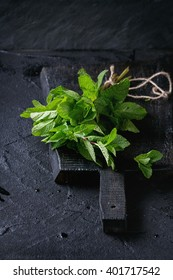 Bunch of fresh mint with thread on black wooden chopping board over black textured background.