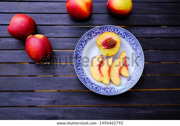 Bunch of fresh nectarines and a plate with a sliced nectarine on a wooden table