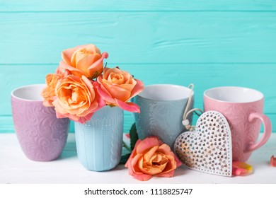 Bunch of fresh orange roses in cup and heart  against  turquoise  wall. Place for text. Floral still life.