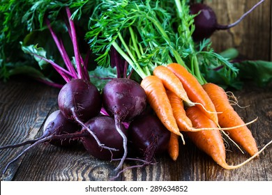 Bunch of fresh organic beetroots and carrots on wooden rustic table