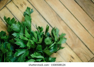 Bunch of fresh parsley celery on a wooden table. Healthy eating, raw food concept background. Fresh greens in the kitchen