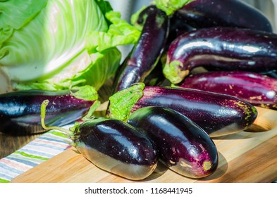 bunch of fresh purple eggplants on a cutting board