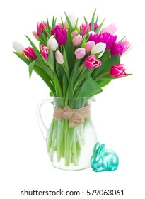 bunch of fresh purple, pink and white tulip flowers in glass vase with rabbit isolated on white background
