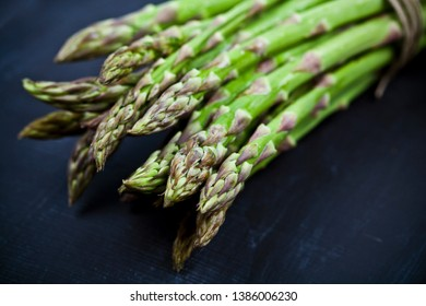 Bunch of fresh raw garden asparagus closeup on black board background. Green spring vegetables. Edible sprouts of asparagus. With copy space.