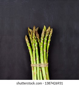 Bunch of fresh raw garden asparagus on black board background. Green spring vegetables.Top view of edible sprouts of asparagus. With copy space.