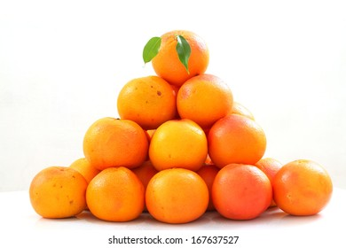 bunch of fresh red grapefruit with green leaf on white background