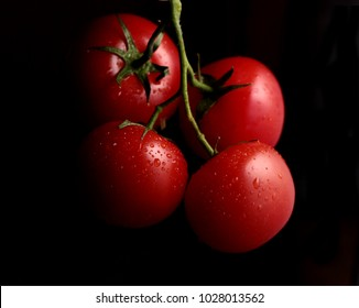 bunch of fresh red tomatoes on dark background