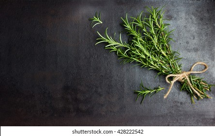 Bunch of fresh rosemary on black background. Top view