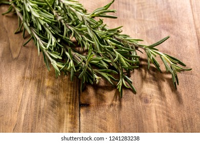 A bunch of fresh rosemary on a wooden board