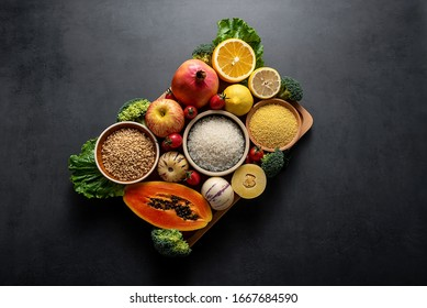 Bunch of fresh seasonal fruits, vegetables and grains of legumes on a black background