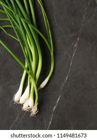 Bunch of Fresh spring onions with bulbs on a grey marble background. High resolution vertical photo