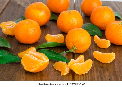 Bunch of fresh tangerines or mandarins and leaves on wooden table. Studio Photo