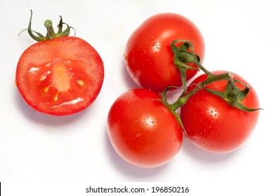 Bunch of fresh tomatoes with water drops. Isolated on white background. Top view.