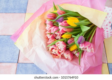 Bunch of fresh tulips wrapped in colorful paper