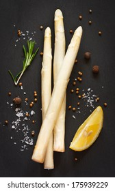 Bunch of fresh white asparagus with rosemary, lemon and spices on a black board.