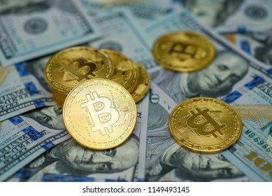 A bunch of gold bitcoin coins laying over hundred dollar bills background