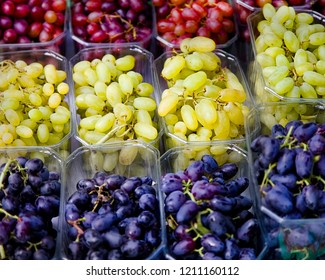 Bunch Of Grape.  Three  table grape varieties in plastic dispensers on display . Closeup. Stock Image.