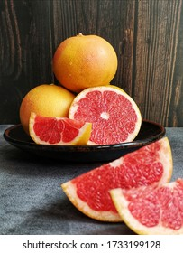 A bunch of grapefruits on a black plate. Two slices of grapefruits placed in front of the image with blurry effect. Grapefruit is a citrus fruit with a flavor that can range from bittersweet to sour.