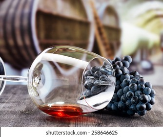 Bunch of grapes and glass of red wine lying on a black wooden table on the background of the wine cellar with barrels.
